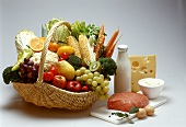Basket of fruit & vegetables, veal & dairy products beside it