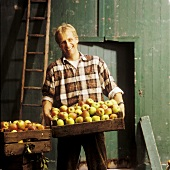 Man holding a crate of apples