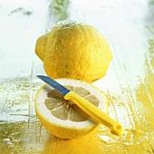 A whole and a half lemon with knife