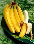 A bunch of bananas and a half-peeled banana