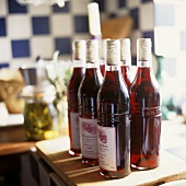 Several bottles of red wine in a kitchen