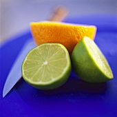 Two lime halves and half an orange