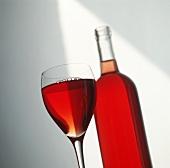 Gefülltes Rotweinglas vor Rotweinflasche