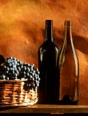 Still life with empty wine bottles & grapes in basket