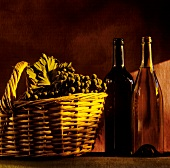 Still life with wine bottles & red wine grapes in basket