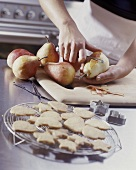 Peeling pears, biscuits in foreground