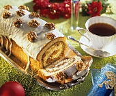 Nut cake roll decorated with glacé icing and walnuts