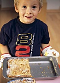 Small boy holding a baking tin with apple cake