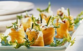 Salmon rolls with cream cheese filling on tray