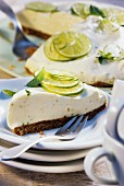 A piece of lime pie in front of pie with piece cut