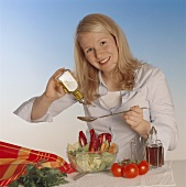 Young woman season mixed salad with oil