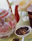 Black tea leaves beside Asian teapot