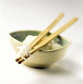 Basmatireis, gekocht, auf Holzstäbchen und im Schälchen