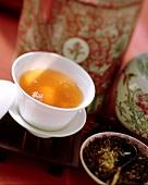 Schwarzer Tee in Trinkschale, daneben Teeblätter im Schälchen