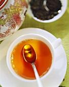 Cup of tea with teaspoon, tea leaves behind
