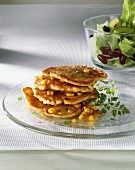 Corn pancakes on top of each other, lettuce in bowl behind