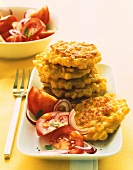Corn pancakes in a pile, with tomato salad