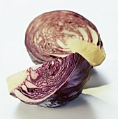 A quarter of a red cabbage lying in front of half a cabbage