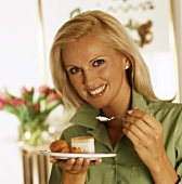 Woman holding plate with a piece of gateau & apricot wedges