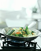 Colourful vegetable stir-fry on gas cooker