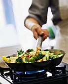 Vegetables being tossed in pan above cooker