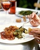 Antipasto plate with marinated potatoes, ham, sausage