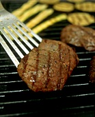 Steak being turned on the barbecue with a spatula