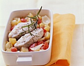 Haddock cutlets on bed of vegetables in baking dish