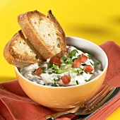 Tomato & spring onion quark with slices of bread in bowl