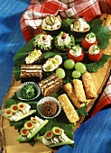 Assorted snacks with cream cheese on a wooden board