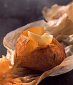 Baked potato with melting butter on baking paper