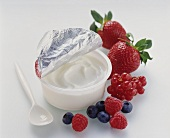 Opened yoghurt pot, fresh berries beside it
