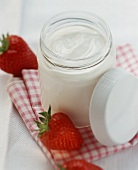 A jar of yoghurt, fresh strawberries beside it