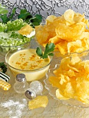 Home-made potato crisps with curry and herb sauces