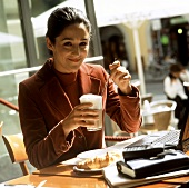 Young woman with latte macchiato sitting in café with laptop