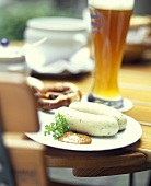 White sausage with pretzel & wheat beer on beer garden table