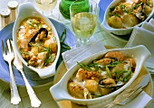Three portions of fish gratin with spring onions and mussels
