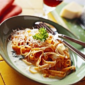 Tomato tagliatelle in cheese sauce, sprinkled with Parmesan