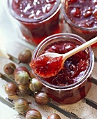 Gooseberry jam in a jar and on a wooden spoon