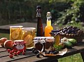 Stillleben mit eingemachtem Obst, Gelee, Likör und Saft