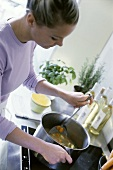 Young woman stirring soup pan on stove