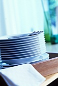 A pile of plates with cutlery