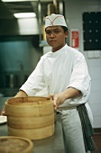 Asian chef with bamboo basket