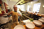 Malaysian chef preparing noodles in the kitchen