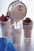 Pouring raspberry milkshake into glass