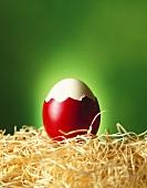 Half shelled Easter egg on straw