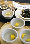 Finger bowls with lemon water for eating mussels