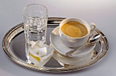 Cup of coffee, glass of water & sugar cubes on silver tray