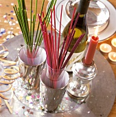 Coloured joss sticks in glasses