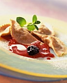 Wholemeal ravioli with apple filling on raspberry puree
